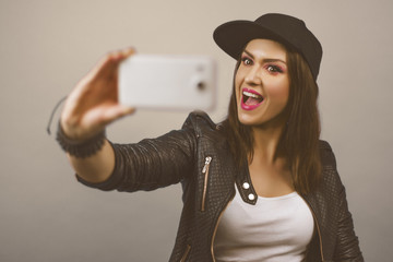 Beautiful young trendy woman with snapback-Cap and black leather