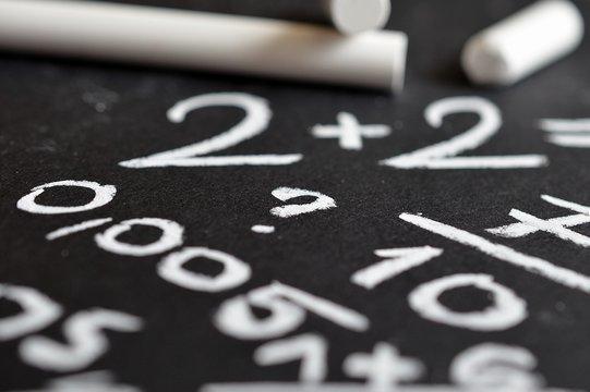 kreda i działania matematyczne na tle czarnej tablicy