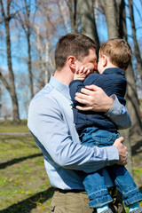 Father and son having fun outdoors on a spring sunny day. Happy smiling little boy in the arms of his dad. Concept of happy family life, love and happiness.