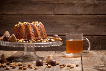 cake, candy, nuts and cup on old wooden background