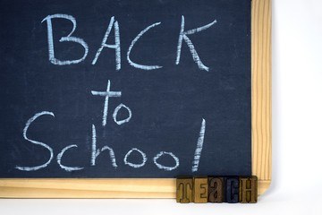 back to school sign on black chalkboard with vintage letterpress type