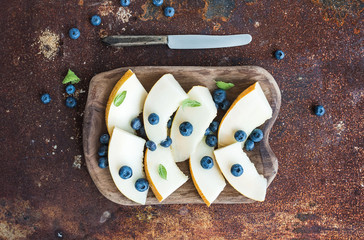 Melon and blueberries in a rustic wooden serving dish
