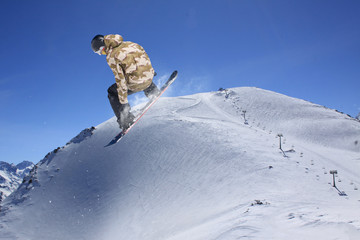 Snowboard rider jumping on mountains. Extreme snowboard freeride.