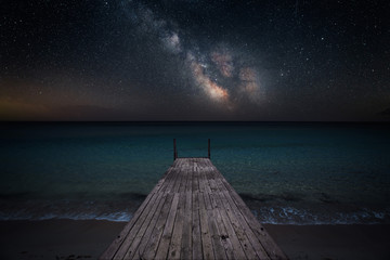Keuken foto achterwand Nacht Milky way over che seashore and small wooden jetty in perspective