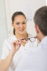Optician giving new glasses to the patient