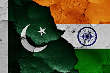 flags of Pakistan and India painted on cracked wall