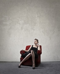Model sitting in a red chair