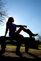 Silhouette of a cowgirl sitting on a bench