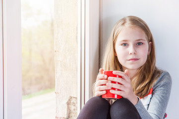 Little beauty girl with cup at the window