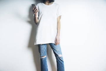 Young stylish woman wearing blank white t-shirt and blue jeans and using smartphone, white background