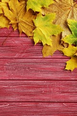 Autumn leafs on a red wooden table