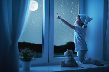 child little girl at window dreaming and admiring starry sky at