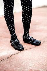 Piernas de mujer con medias negras con lunares blancos .
