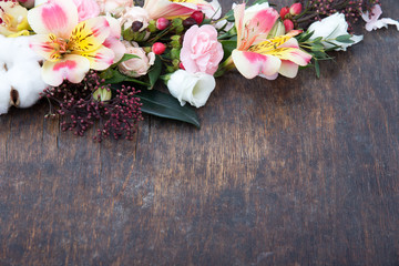 Flowers frame on wooden background