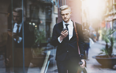 Serious professional lawyer using smart phone while walking on the street during a break near his office outside, flare light