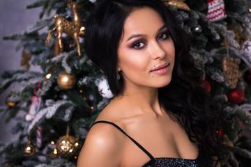 Portrait of elegant young woman in evening dress over christmas background, fashion beauty photo