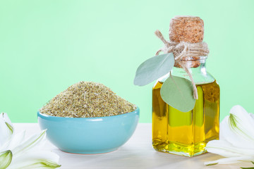 Dry camomile in a bowl and a bottle of organic oil.