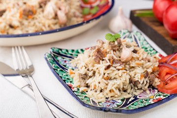 Traditional uzbek pilaf (plov) with tomatoes and red onion
