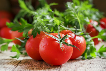 Wet red tomatoes, herbs, close-up shot, shallow depth of field,