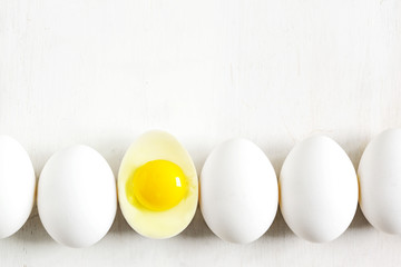 White eggs lined up on a white wooden background