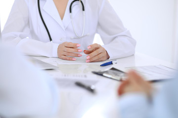 Medical doctor and young couple patients discussing something at the table . Hands close-up