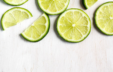 Lime slices on white wooden background