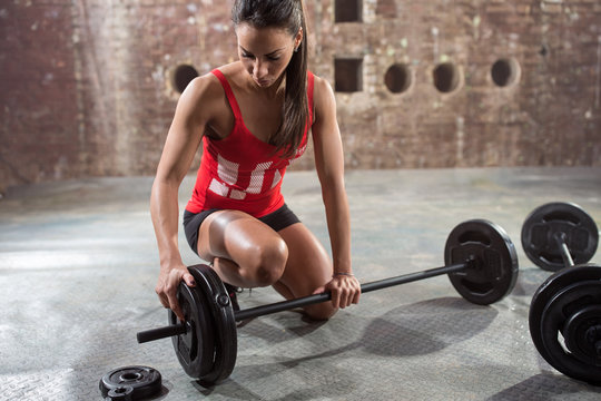 fitness woman preparing to lift some heavy weights.
