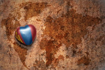 heart with national flag of mongolia on a vintage world map crack paper background.