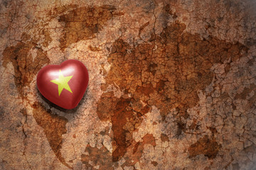 heart with national flag of vietnam on a vintage world map crack paper background.