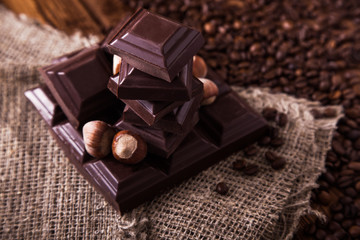 Roasted coffee beans, chocolate and nuts on the wooden background