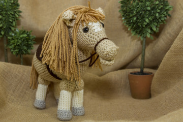 A handcrafted crochet toy horse photographed on a rustic burlap backdrop.
