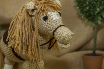 A close-up image of a handmade crocheted toy horse photographed on a rustic burlap background.