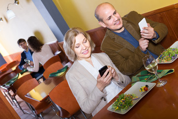 senior couple busy with phones on date in cafe