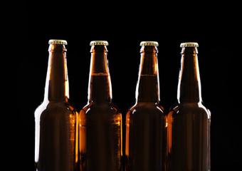 Four bottles of beer on black background