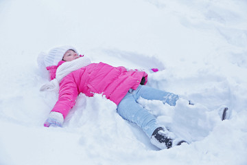 Little girl with winter clothes lying on the snow outdoor