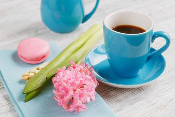 Cup of black coffee, pink flowers and french macaroons