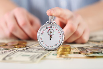 Time is money concept. Stopwatch  on the table with money, close up