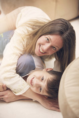 Happy mother and son smiling at home