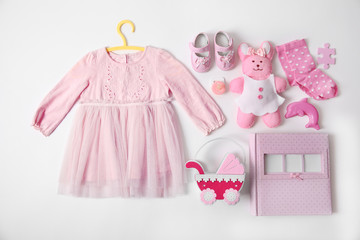 Baby clothes with toys and photo album on white background