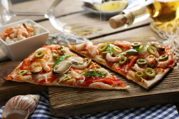 Pizza slices with seafood, red pepper, green olives and bottle of wine on wooden table