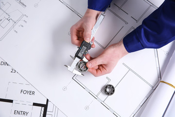 Male hands using divider on a blueprint, top view