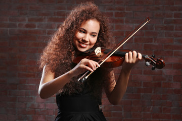 Beautiful young woman playing violin over brick wall background