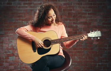 Beautiful young woman playing on guitar over brick wall background