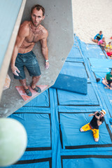 Male climber before jump on artificial climbing wall, photographer taking picture from beneath