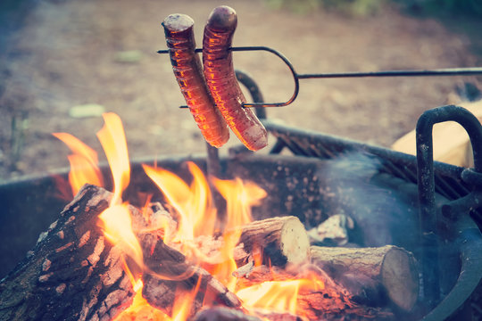 Preparing sausages on campfire, dinner on camping vacation