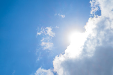 Looking up at Nice blue sky with sun beam behind big cloud