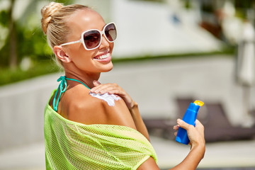 Close up of young woman in sunglasses putting sun cream on shoul