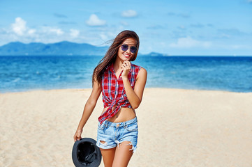 Pretty young woman portrait posing on the beach over blue sky an