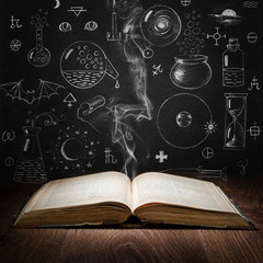Opened magic book with alchemy symbols on chalkboard. Philosophy, spirituality, occultism, chemistry, science, alchemy and magic symbols.