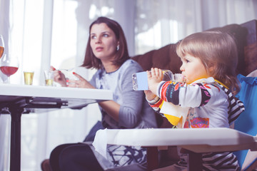 Mother with baby eating in a restaurant.